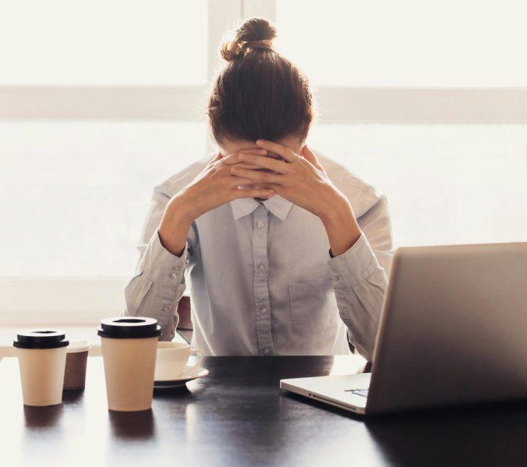 Imagem de senhora cansada no trabalho cercada de café. GeneWei.com